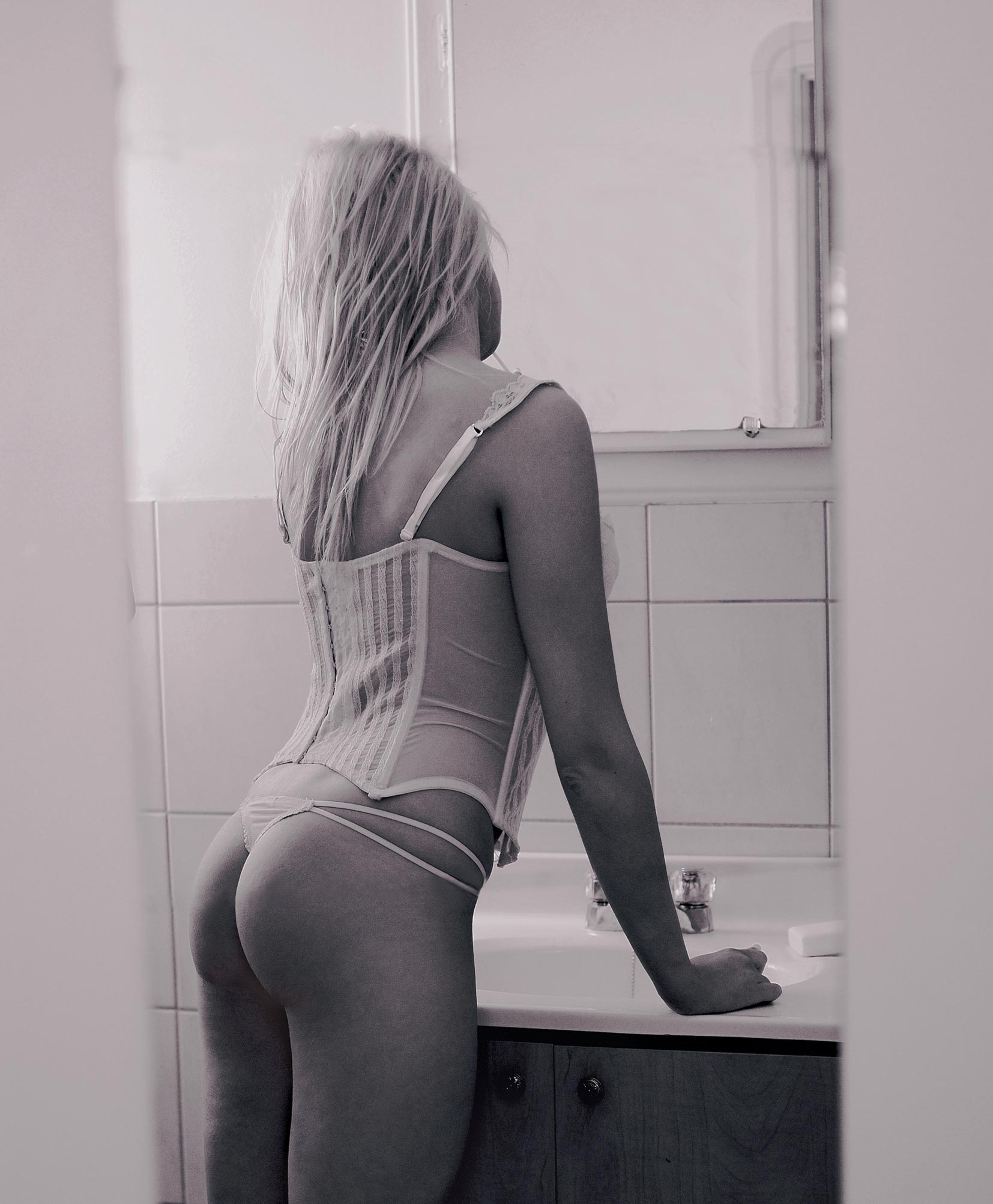 Photo noir et blanc de boudoir devant un miroir / femme à la vanité portant de la lingerie blanche