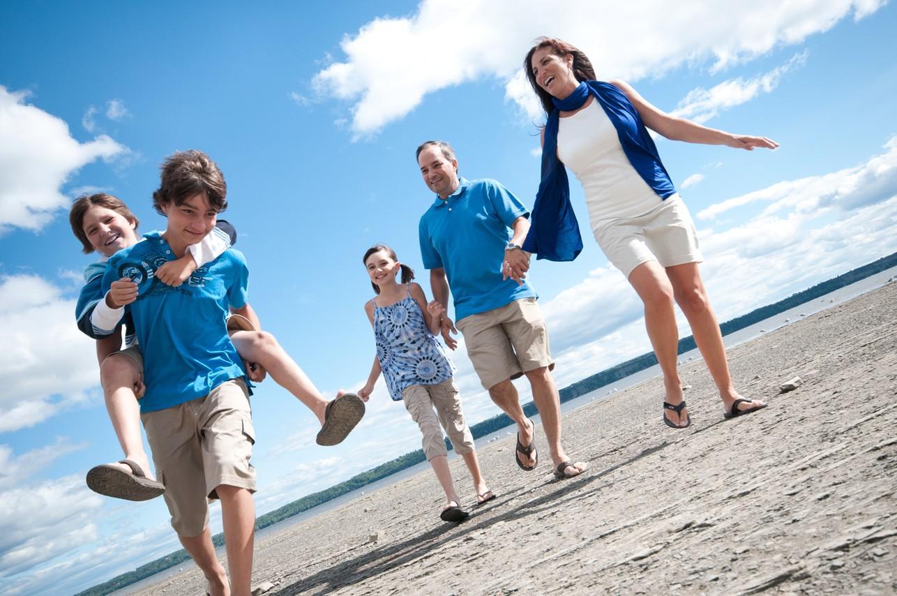 Portrait extérieur d'une famille courant sur le bord de l'eau / Photographe de portrait professionnel dans Portneuf, Québec