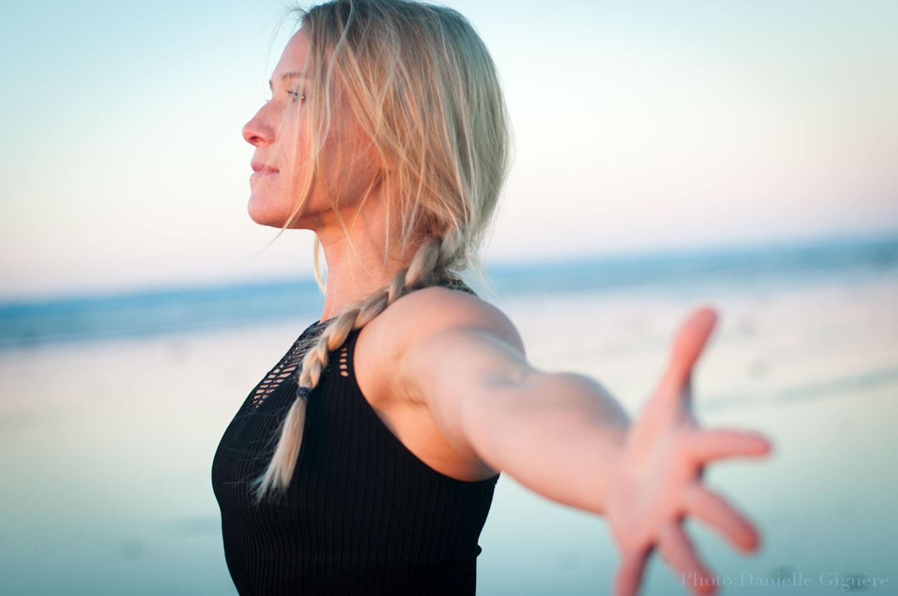 France Girard en pose de yoga les bras ouverts sur le bord de l'eau / Studio Ambre-Rebel