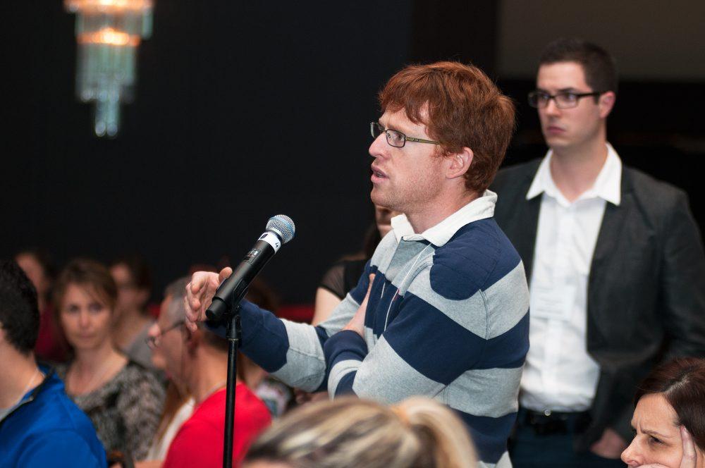 Participant au micro durant la période de question d'une conférence / Événement corporatif