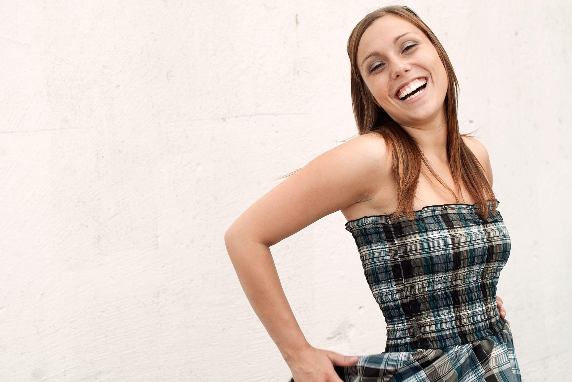 Photo naturelle d'une jeune femme rigolant devant un mur blanc / Portrait en lumière ambiante