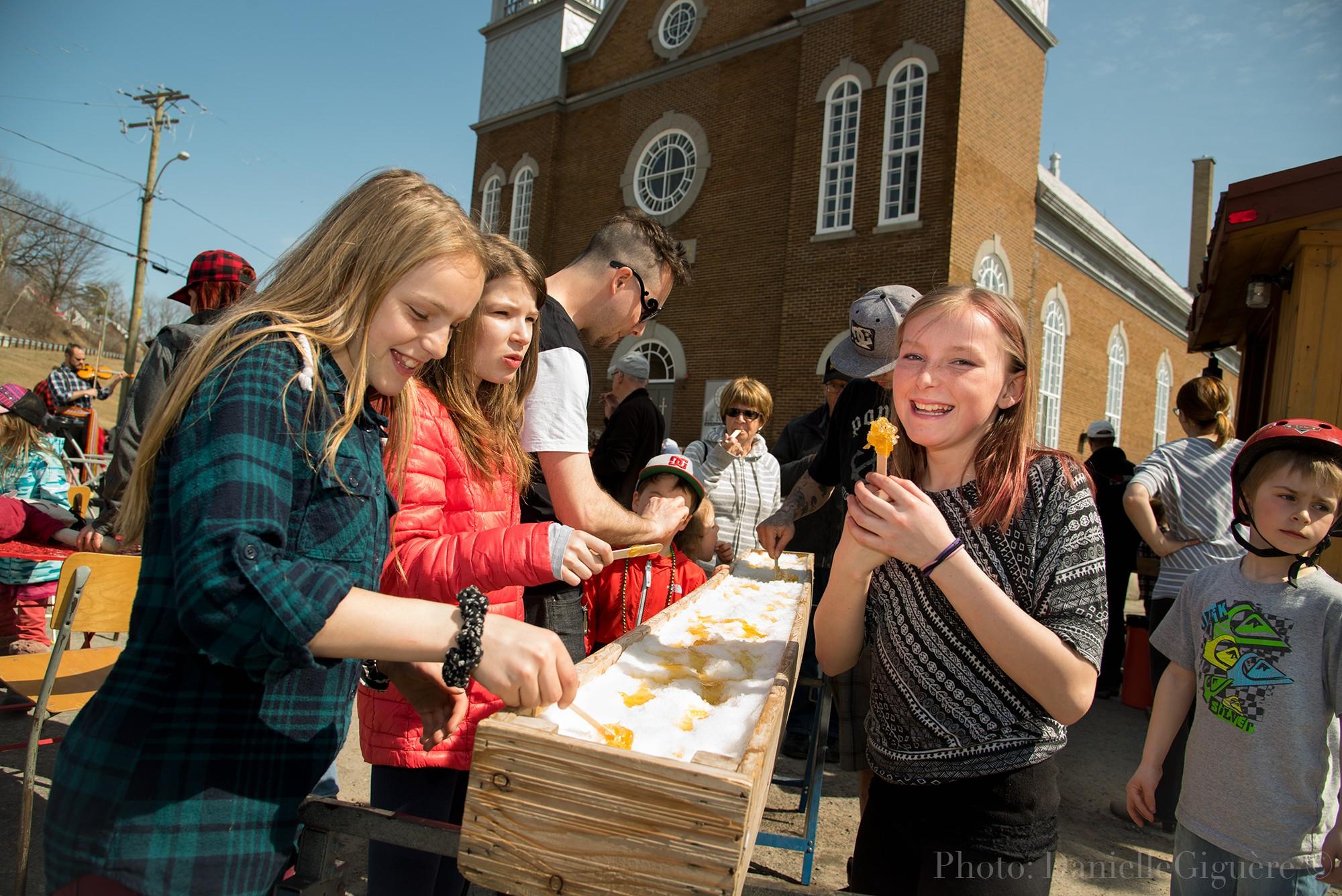 Participants mangent de la tire d'érable à la fête de Pâques à Donnacona