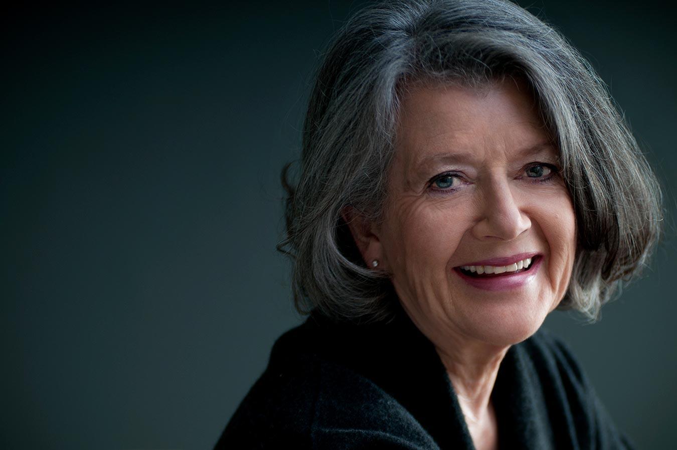 Photo d'un femme mature aux cheveux gris souriante et naturelle / Séance photo de portrait en studio